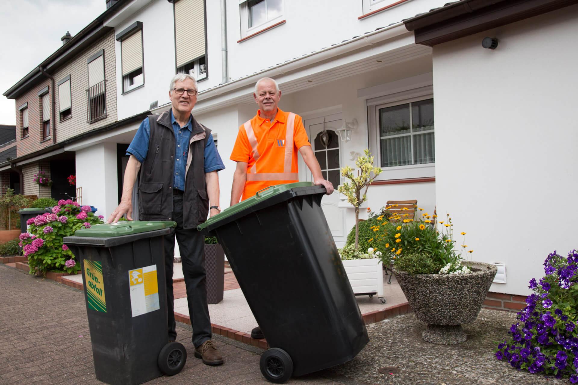Mitarbeiter der Entsorgung bei der Arbeit mit zwei Mülltonnen