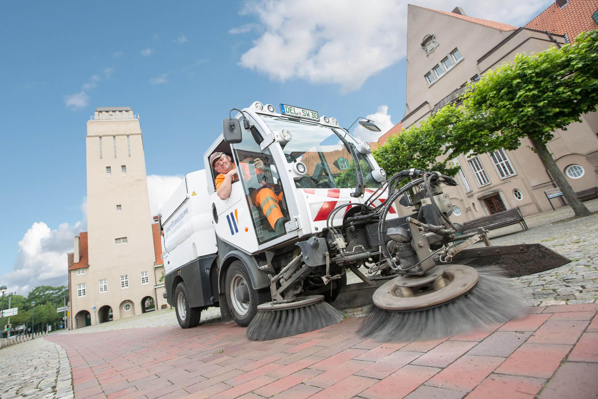 Mitarbeiter in Straßenreinigungsfahrzeug