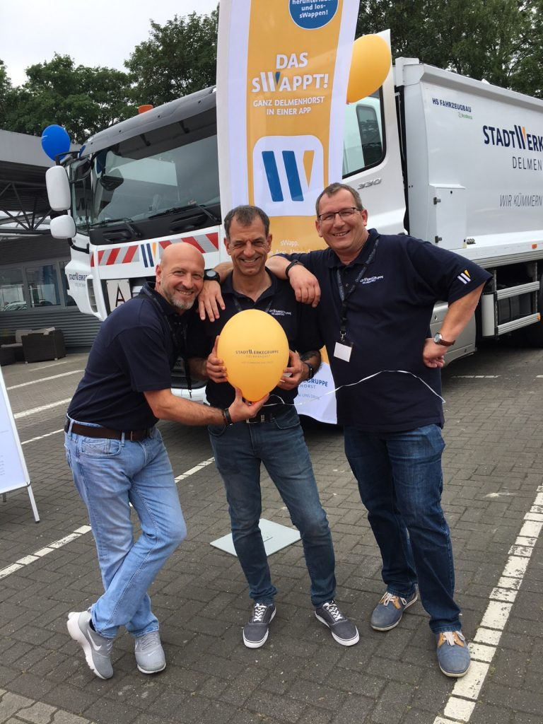 Mesut Canakci, Michael Rocco und Frank Heinrichs gemeinsam vor LKW mit Luftballon